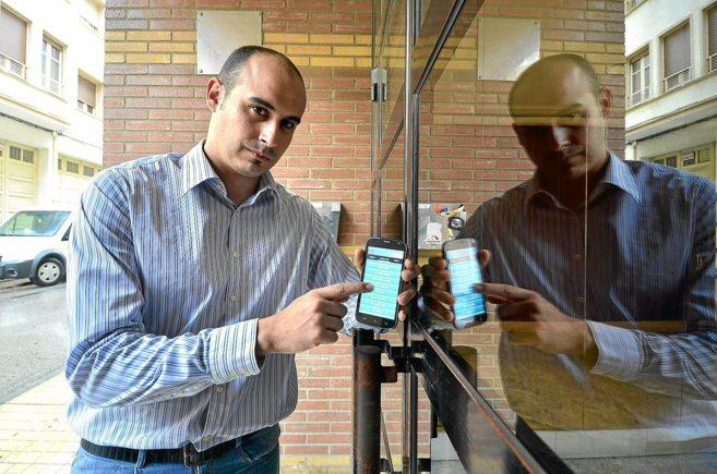 Ángel Ortiz muestra un teléfono móvil con la aplicación que ha...