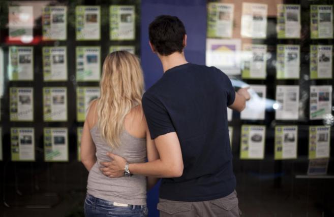 Una pareja mira anuncios de viviendas en un escaparate de Look and...