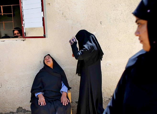 Varias mujeres lloran en el funeral de siete de sus familiares en...