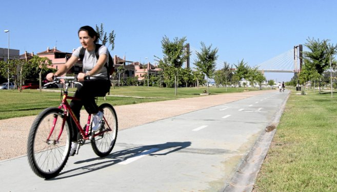 Una ciclista circula por el carril bici del nuevo parque abierto sobre...