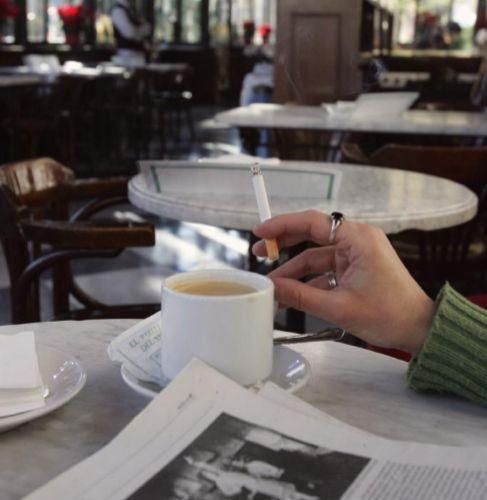 Una mano de mujer sostiene un cigarro mientras sostiene una taza de...