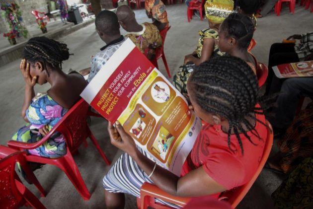 Una mujer lee un cartel con información sobre el virus del ébola en...
