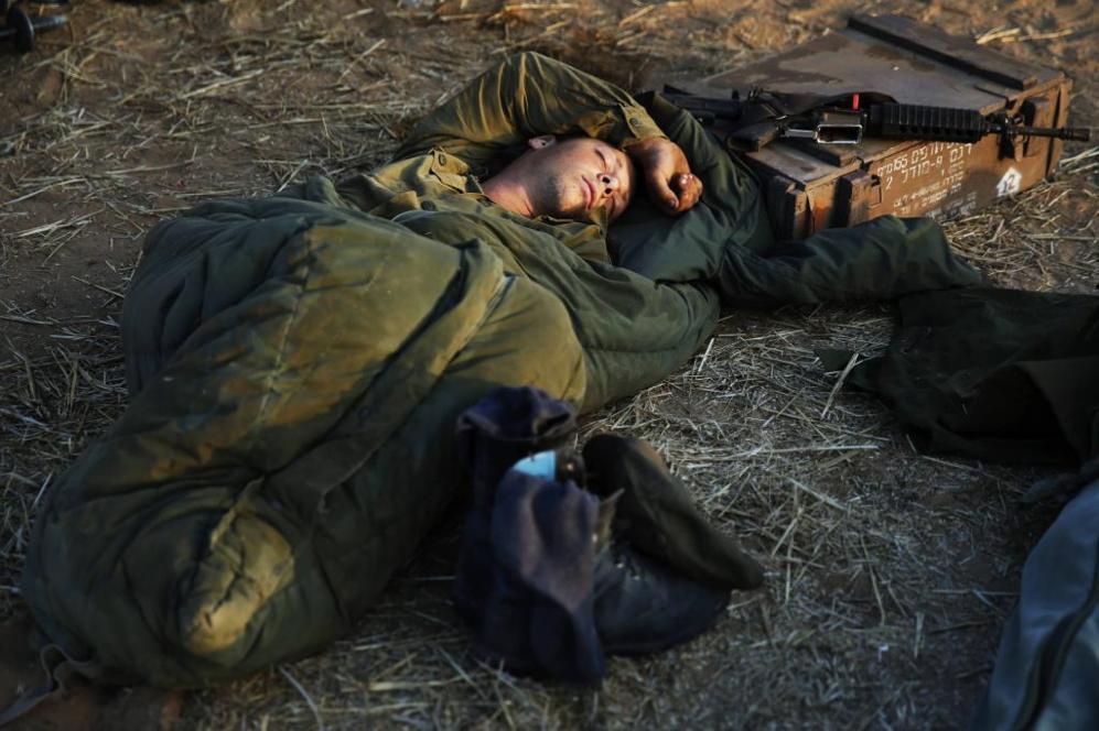 Un soldado israelí duerme en un campo cerca de la Franja de Gaza.