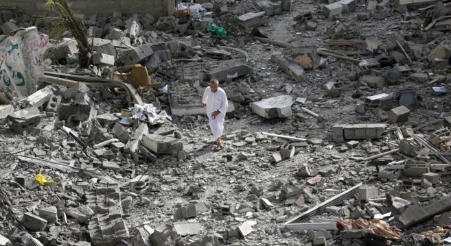 Un hombre palestino camina entre los escombros de una casa bombardeada...