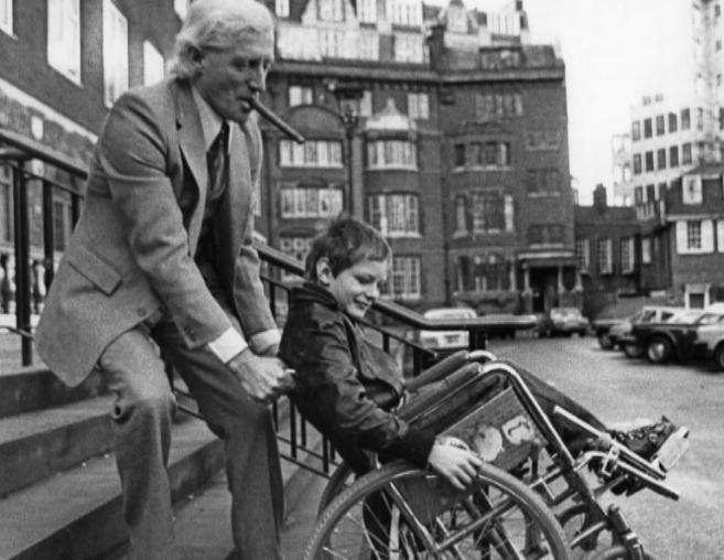 Savile ayuda a un niño en silla de ruedas en 1980.