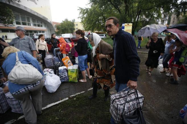 Residentes en Donetsk se preparan para tomar un autobús hacia Rusia.