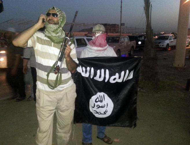 Un miliciano del IS muestra un arma mientras otro sujeta una bandera...