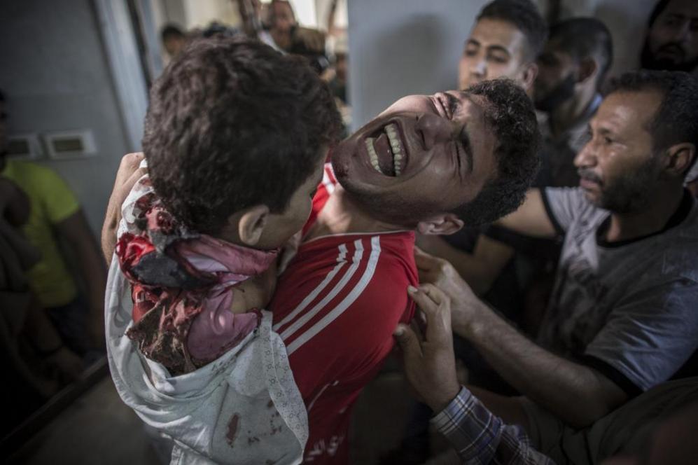 Un joven palestino llora mientras sujeta el cuerpo sin vida de su...