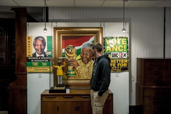Un joven observa un retrato de Nelson Mandela en una exposición en...