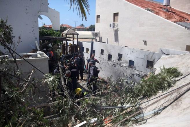 Trabajadores de emergencia entran en una casa que sufrió el impacto...