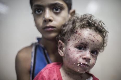 Un niño palestino de 9 años sostiene a su hermana de un año y medio...