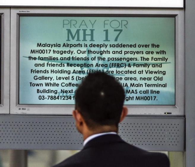 Un pasajero observa un panel de información en el aeropuerto de Kuala...