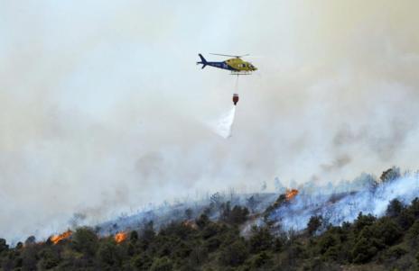 Un helicóptero trabaja en la extinción del incendio declarado en...