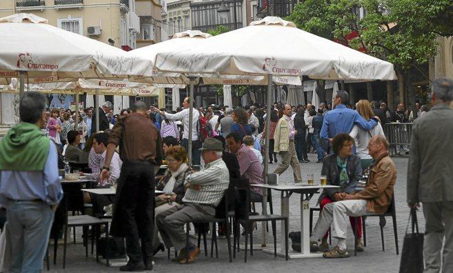 Un grupo de personas toma un aperitivo en los veladores de un bar en...