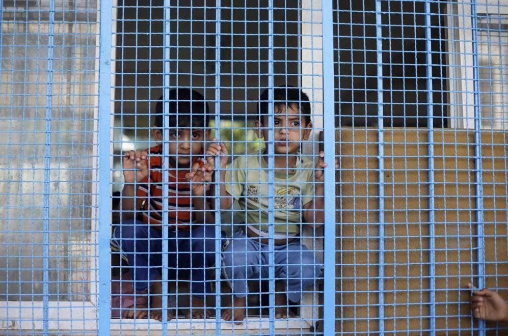 Dos chavales palestinos se protegen en la escuela de la ONU de la...