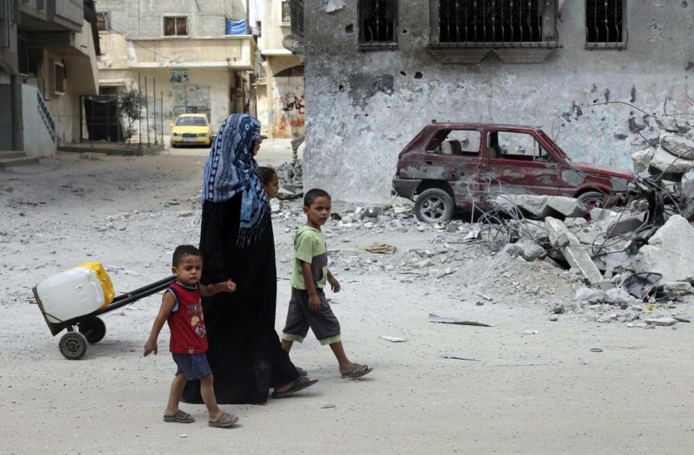 Una madre y de su hijo pasan junto a un coche destrozado.