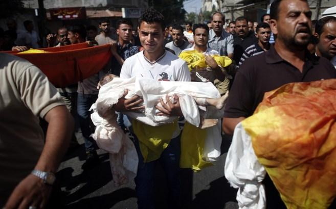 Un hombre con el cadáver de un niño, fallecido en el ataque israelí...