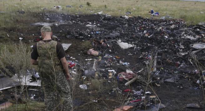Un rebelde prorruso observa varios cadáveres entre los restos del...
