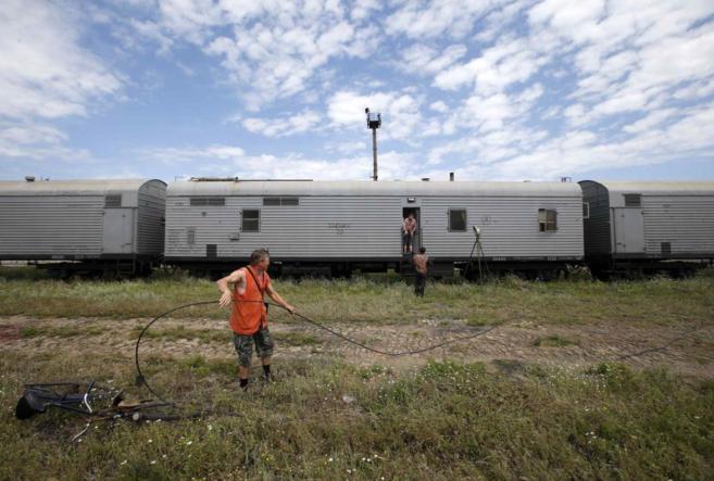 Empleados ferroviarios, junto a los vagones refrigerados que...