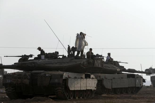 Un soldado israelí se ajusta un talit sobre un tanque.