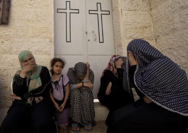 Varias mujeres palestinas se refugian en una iglesia ortodoxa del...
