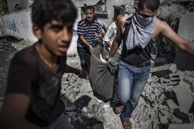 Varios palestinos recuperan un cadáver de debajo de los escombros de...