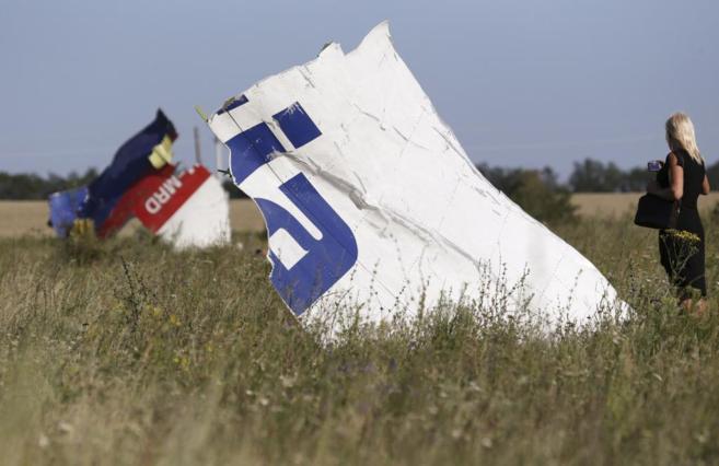 Una mujer toma hoy una fotografía de los restos del avión de...