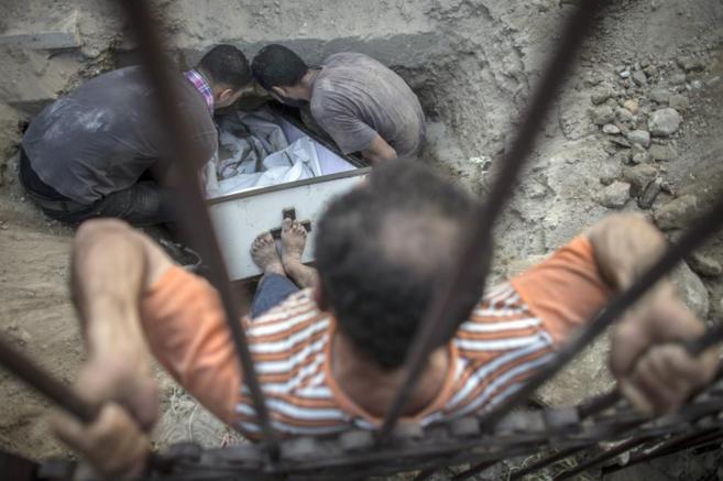 Un palestino intenta enterrar el ataúd de una de las victimas de los...
