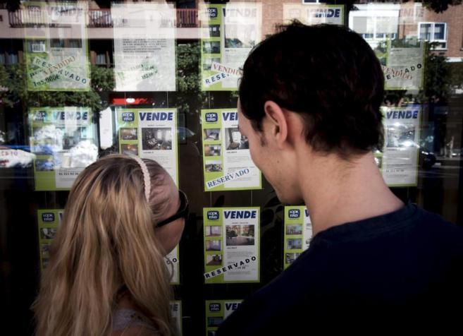 Una pareja observa los anuncios de ofertas inmobiliarias.