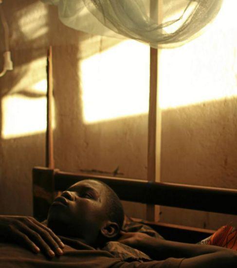 Un joven diagnosticado de malaria reposa en una cama con mosquitera.