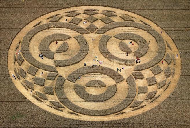 Varias personas, que no son más que puntos, pasean entre el círculo