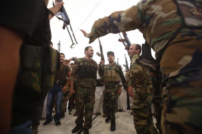 Combatientes chiíes alzan sus armas durante un entrenamiento en...