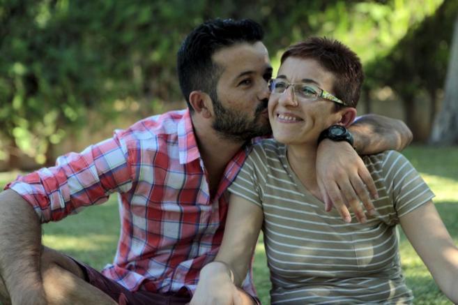 Un joven besa a su hermana en la mejilla sentados en un jardín
