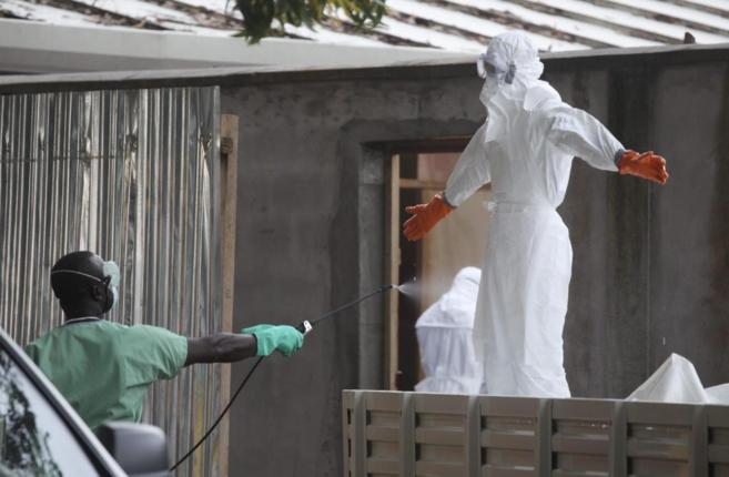 Enfermeros liberianos son fumigados con desinfectante antes de...