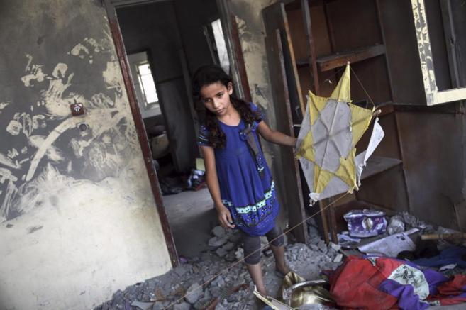 Una niña palestina rescata su cometa de entre los escombros de su...