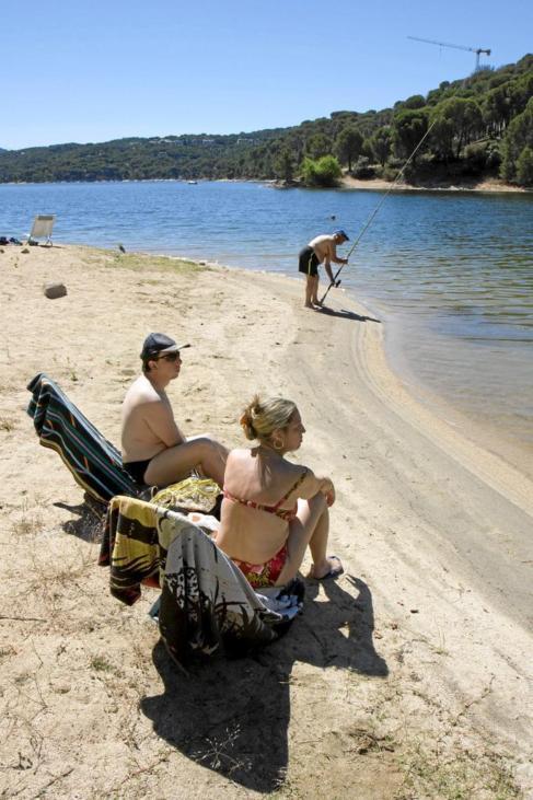 Dos bañistas toman el sol en la orilla del Pantano de San Juan.