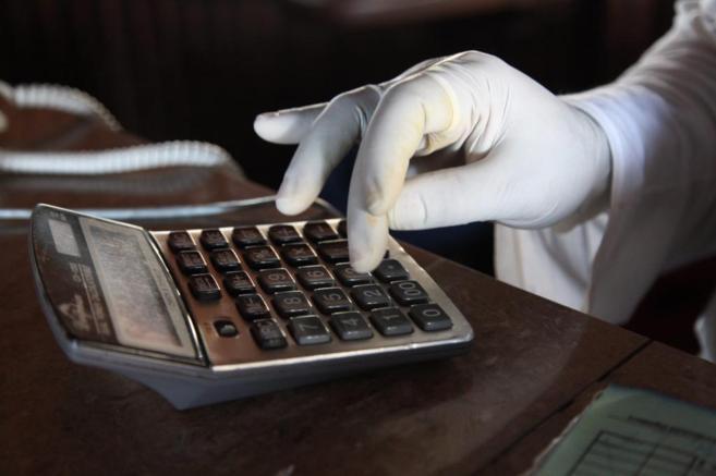 Un recepcionista liberiano usa una calculadora con guantes para evitar...