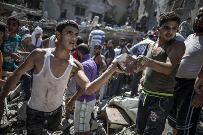 Un palestino sostiene una piedra ensangrentada en el campo de...