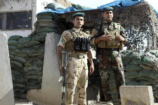 Efectivos kurdos, a la entrada de un edificio oficial en el Kurdistán...