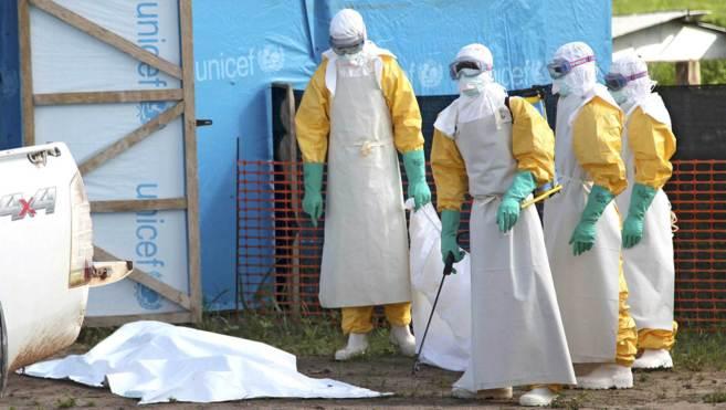 Varios sanitarios, protegidos con trajes especiales, en una zona de...