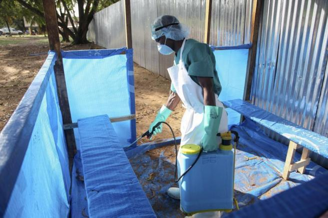 Una enfermera desinfecta una zona cercana a un centro médico en...