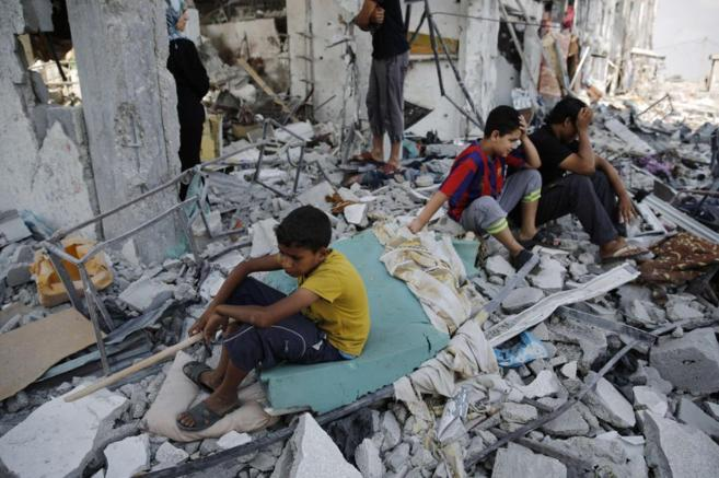 Niños palestinos sobre los escombros de su casa en Beit Hanoun,...