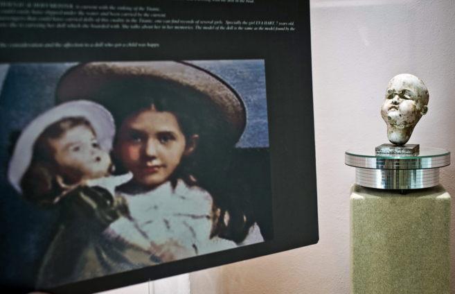 Lo que queda de la muñeca, junto a una fotografía de la niña que la...