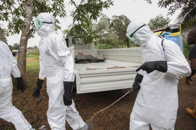 Enfermeros liberianos se desinfectan después de trasladar el cadáver...