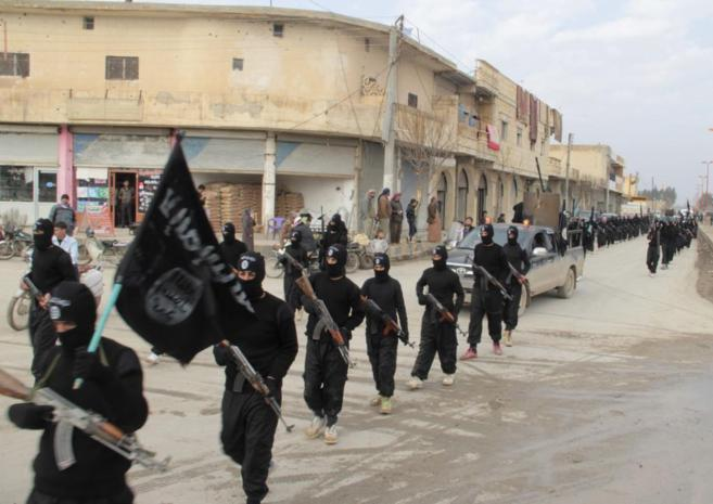 Miembros del Estado Islámico (IS) desfilan por Tal Abyad, en la...