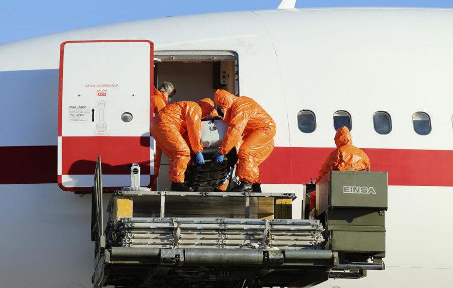 Operarios bajan la camilla del avión que transporta a Pajares.