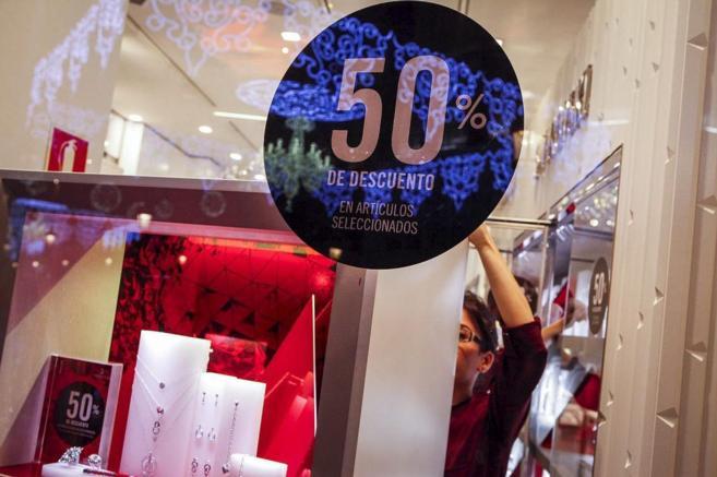 Una mujer en su establecimiento junto a un cartel del 50% de...