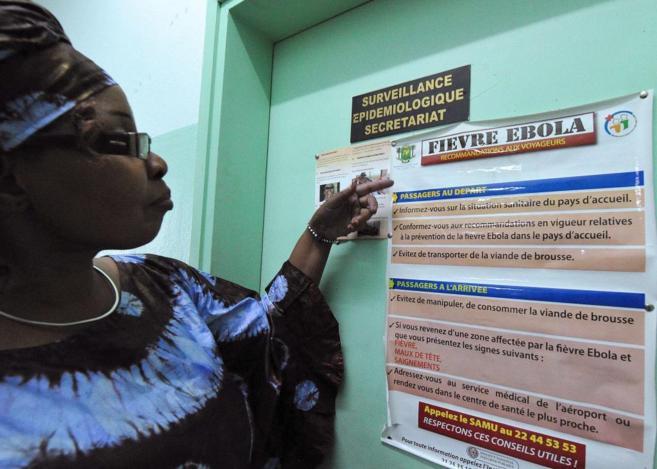 Una mujer lee un póster con información sobre el ébola en Nigeria.