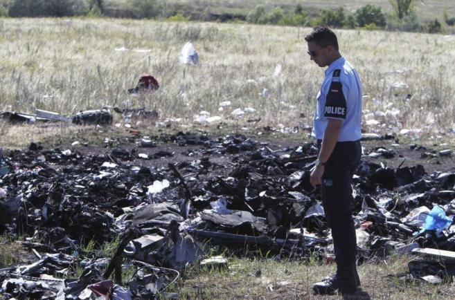 Un policía examina los restos de la aeronave en Grabovo, al este de...