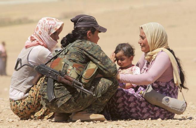 Una miembro de las fuerzas kurdas ayuda a desplazados yezidis que...